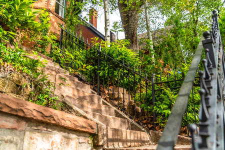 Sunlit stone stairway with black metal railing and brick house background. Sunny day views at the exterior of a residence with outdoor stairs and lush foliage. Archivio Fotografico