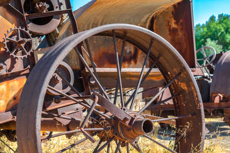 Close up of the rusty wheels of an old vintage tractor on a farm on a sunny day