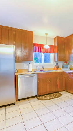 Vertical Spacious kitchen with plenty of amenities, square tile floor and warm lighting. Wonderful California home in San Diego county. Real estate listings with powerful visuals.