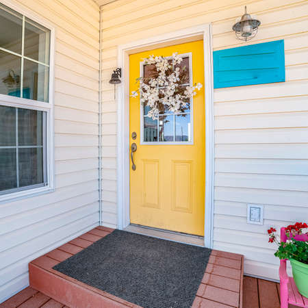 Square Bright yellow front door to a white wooden house decorated with a spray of flowers under a covered porch Stock Photo