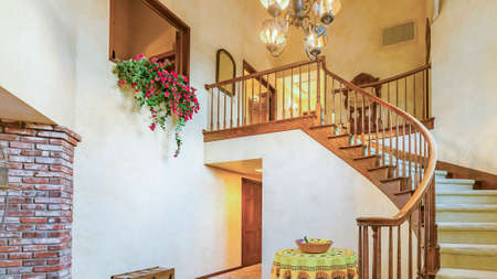 Panorama frame Spiral stairs in rustic entry of a luxurious California home with warm lighting. Wonderful California home in San Diego county. Real estate listings with powerful visuals.