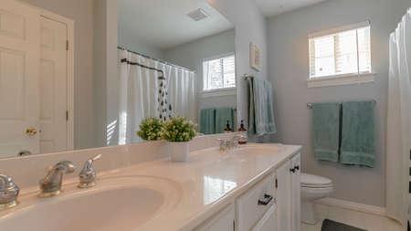 Panorama Modernes, luxuriöses weißes Badezimmer-Interieur mit Waschtischunterschränken, Spiegel, Toilette und Duschkabine in einer zurückweichenden Ansicht