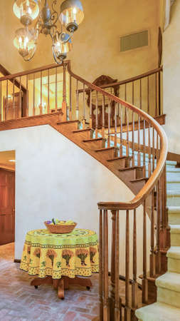 Vertical frame Spiral stairs in rustic entry of a luxurious California home with warm lighting. Wonderful California home in San Diego county. Real estate listings with powerful visuals.