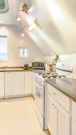 Vertical Bright, open and warm kitchen with vaulted ceilings and stove top. Wonderful California home in San Diego county. Real estate listings with powerful visuals.