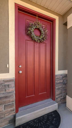 Vertical Colourful red entrance door to a house with wreath in a modern urban housing development