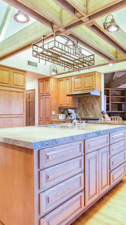 Vertical frame Bright, open and warm kitchen with vaulted ceilings and island with spotlights. Wonderful California home in San Diego county. Real estate listings with powerful visuals.