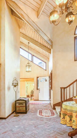 Vertical Two chandeliers in a warm cottage style home with stone floors. Wonderful California home in San Diego county. Real estate listings with powerful visuals.