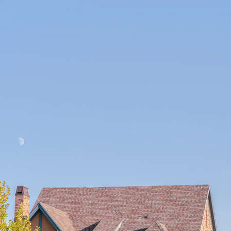 Square frame Steeply pitched house roof with dormer windows viewed past leafy green trees under a sunny blue sky Stockfoto