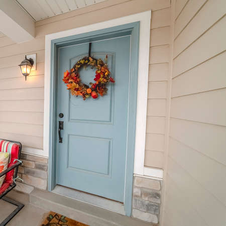 Square Colorful red outdoor chairs on a covered patio alongside an entrance door to a house decorated with a wreath