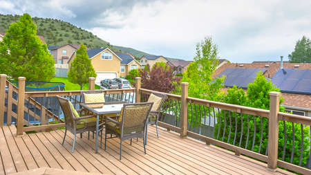 Pano Deck overlooking solar panels on roof of home against mountain and cloudy sky. The deck has wooden floor, furniture, and stairs that leads down to the yard.