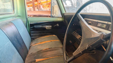 Pano Old vintage car with close up of the steering wheel and dirty interior. The rusty car has peeling green paint and damaged front seats.
