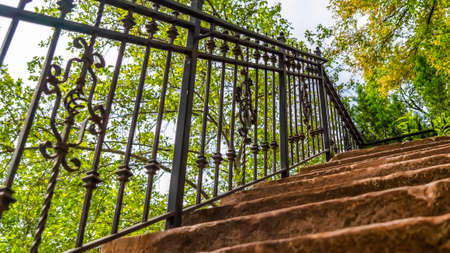 Pano frame Close up of staircase with stone treads and metal railing against leaves and sky. Outdoor stairway against a stone wall viewed on a sunny day.