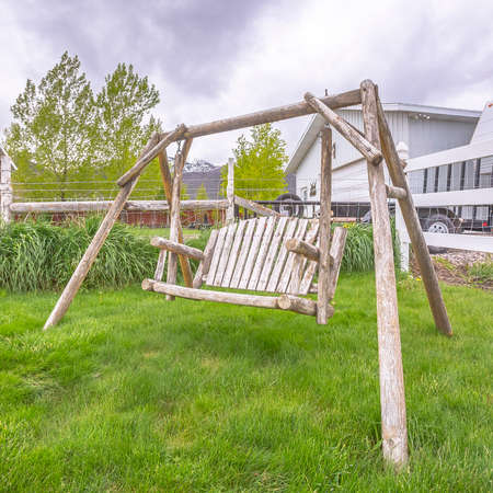 Square Wooden bench swing at the lush grassy yard of a home with white picket fence