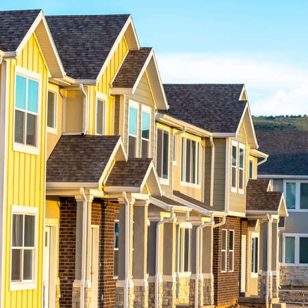 Square frame Townhouses with gable roof and stairs at the entrance framed by square columns. Sunny day view of residences with wood and brick exterior wall.