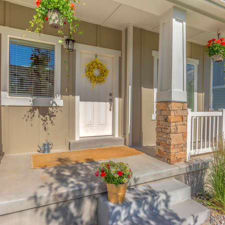 Square Outdoor stairs porch and white front door with wreath at the facade of a home. Colorful potted plants adorn the entrance of the sunlit house.
