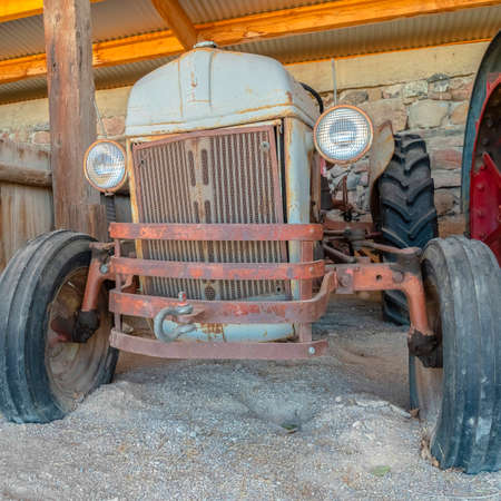 Square Front of an old and vintage tractor against stone wall and roof of a farm barn. The rusty abandoned farming equipment has round headlights.