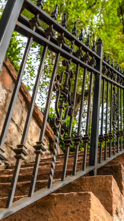 Vertical frame Close up of metal railing and stone treads of a staircase against stone fence. Outdoor stairway with lush green trees and bright sky in the background.