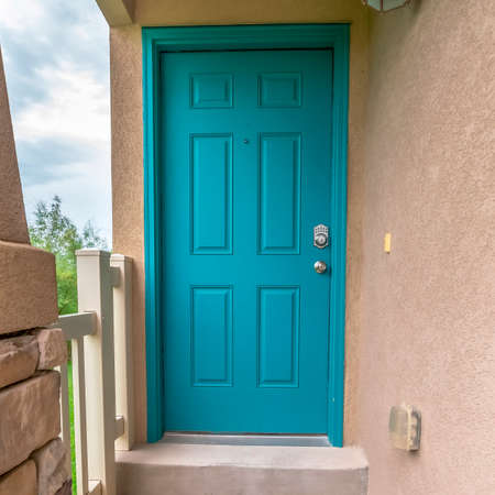 Square Close up of home entrance with blue green front door and concrete exterior wall. A doormat, white railing, and stone pillar can also be seen at the facade of this house. Stock Photo