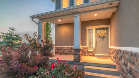 Pano Home entrance with pathway and stairs leading to porch and door with wreath Stock Photo