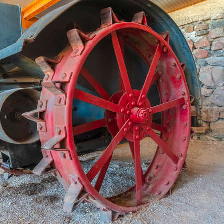Square Red wheel rim of an and vintage tractor against stone wall of a farm barn. The abandoned and weathered farming equipment has a rusty body. 版權商用圖片