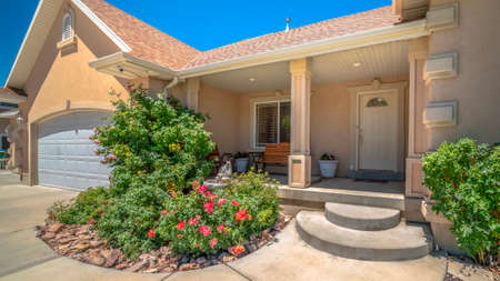 Pano Pathway leading to garage and stairs of a home with porch and landscaped yard. Beautiful view of a house exterior against blue sky on a sunny day.
