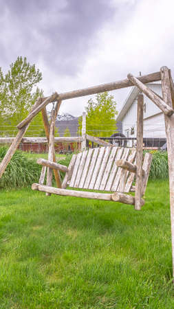 Vertical Wooden bench swing at the lush grassy yard of a home with white picket fence. Close up of an old garden swing with houses, vehicle, and cloudy sky in the background.