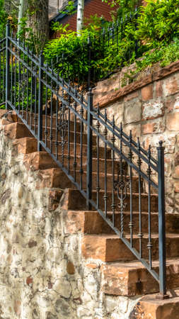 Vertical Outdoor staircase with stone steps and black metal railing against a fence Archivio Fotografico