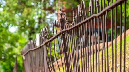 Pano frame Close up of old and rusty iron fence against grassy slope ground and lush trees. The metal guardrail is on top of a stone support wall.