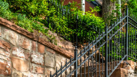 Pano frame Outdoor staircase with stone steps and black metal railing against a fence. Close up of a sunlit stairway with house and plants at the top.