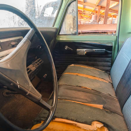 Square frame Old vintage car with close up of the steering wheel and dirty interior. The rusty car has peeling green paint and damaged front seats.