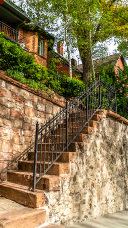 Vertical Outdoor staircase against stone fence of home with red brick wall and balcony. The stairway has rustic stone treads and black metal railing.