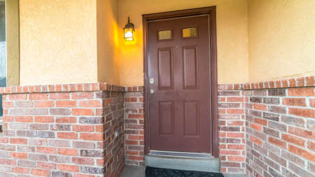 Pano frame Brown door with glass panels of a home with concrete and brick exterior wall. A sliding window, doormat, and wall lantern can also be seen at the facade of this house.