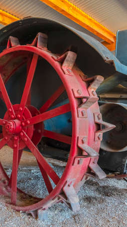 Vertical frame Red wheel rim of an and vintage tractor against stone wall of a farm barn. The abandoned and weathered farming equipment has a rusty body. 版權商用圖片 - 137184738