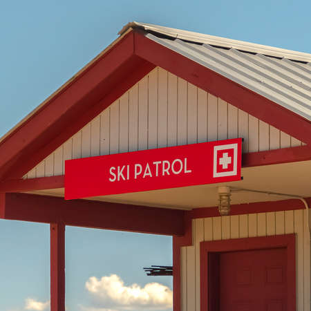 Square frame Ski Patrol building with stairs going to porch and red front door in Park City. Scenic views at a ski resort with mountain and blue sky bakcground at off season.