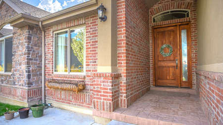 Pano Brick house with arched entrance leading to front door with sidelight and wreath. Shiny windows, landscaped yard, and blue sky with clouds can also be seen on this sunny day.