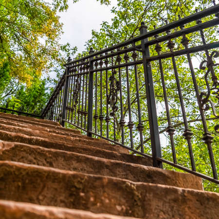 Square Close up of staircase with stone treads and metal railing against leaves and sky