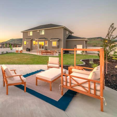 Vierkant houten meubilair op de patio van een grijs huis tegen berg en lucht bij zonsondergang. Buiten leefruimte op het erf met weelderig gazon en witte omheining. Stockfoto
