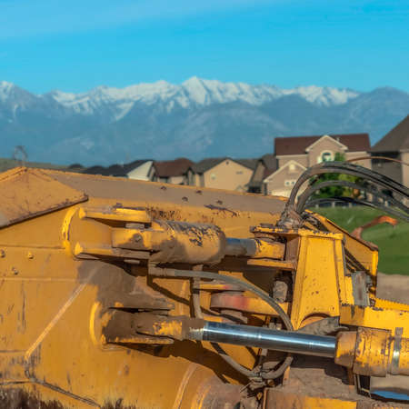 Square Yellow bulldozer with close up view of the mechanism at the back of the blade. Construction machinery with snow capped mountain and blue sky in the blurry background.