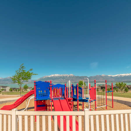 Square Fun colorful childrens playground overlooking lake snowy mountain and blue sky. Recreational park with the play area surrounded by half circular white fence.