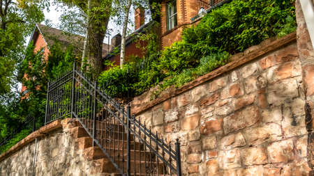 Pano frame Outdoor staircase against stone fence of home with red brick wall and balcony. The stairway has rustic stone treads and black metal railing.