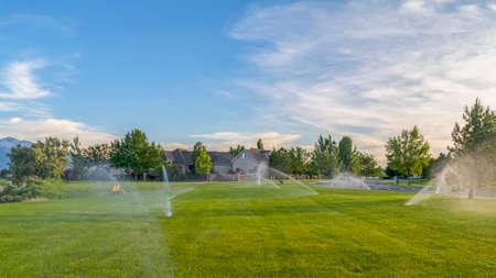 Cadre panoramique Arroseurs pulvérisant de l'eau sur les herbes vertes avec vue sur la montagne et le ciel bleu des maisons. Nature pittoresque et paysage résidentiel avec système d'irrigation automatique.