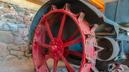Pano Red wheel rim of an and vintage tractor against stone wall of a farm barn. The abandoned and weathered farming equipment has a rusty body. 版權商用圖片