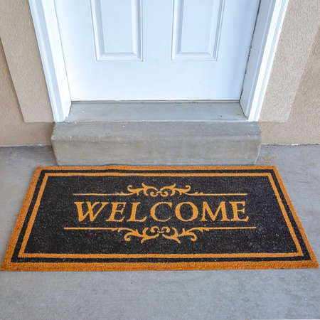 Square frame Black and brown Welcome doormat by the doorstep of home with white front door. Close up view of the entryway of a house with concrete floor and wall.