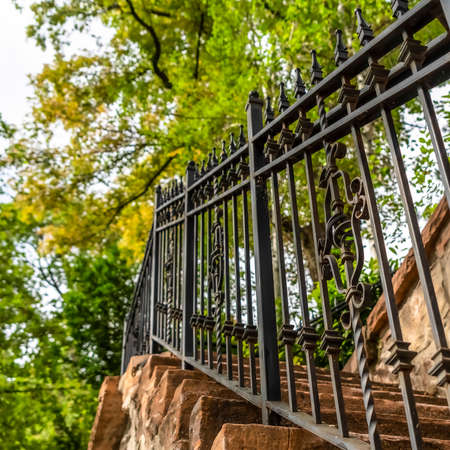 Square Close up of metal railing and stone treads of a staircase against stone fence. Outdoor stairway with lush green trees and bright sky in the background.