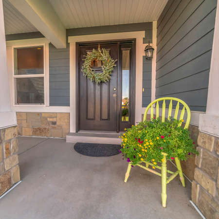 Square Porch and facade of home decorated with colorful flowers and wreath on the door