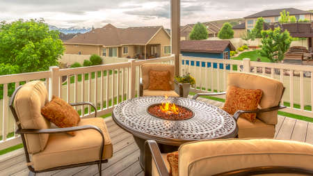 Pano frame Chairs around table with fire pit at a residential balcony framed with railings