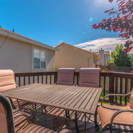 Mesa cuadrada y sillas en el balcón de una casa con escaleras que bajan al patio. El espacio de vida al aire libre tiene una vista tranquila de los árboles y el cielo azul en un día soleado. Foto de archivo