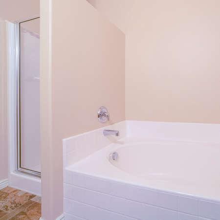 Interno quadrato di un piccolo bagno luminoso con vasca e arredamento beige neutro in una vista ravvicinata