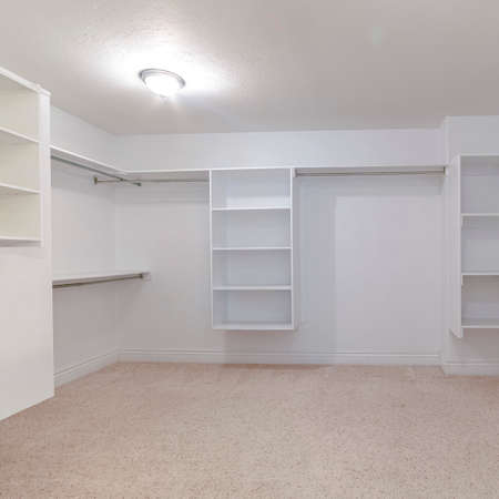 Square Empty white shelves in a large fitted walk-in wardrobe or dressing room with hanging rails for clothes