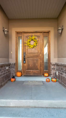 Vertical Pumpkins and wreath decoration for autumn or Halloween arranged on the covered entrance porch of a house